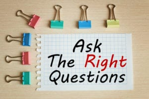 Bulldog clips with writing on paper that reads 'ask the right questions'