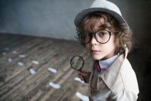 Young boy in with magnifying glass